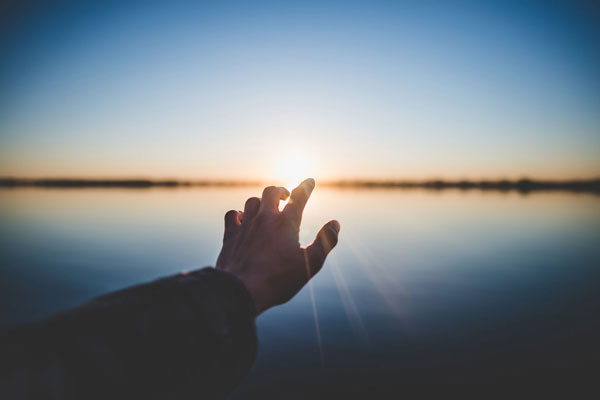 Grief Recovery - Hand pointing at the sun.